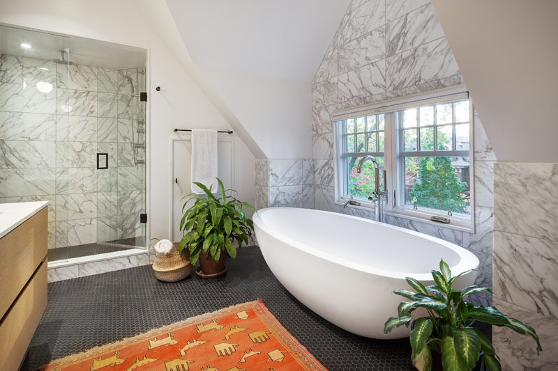 In this contemporary bathroom, high ceilings create a lofty feeling, while the freestanding white bathtub is positioned in front of the window that has tree views. #BathroomDesign #ModernBathroom