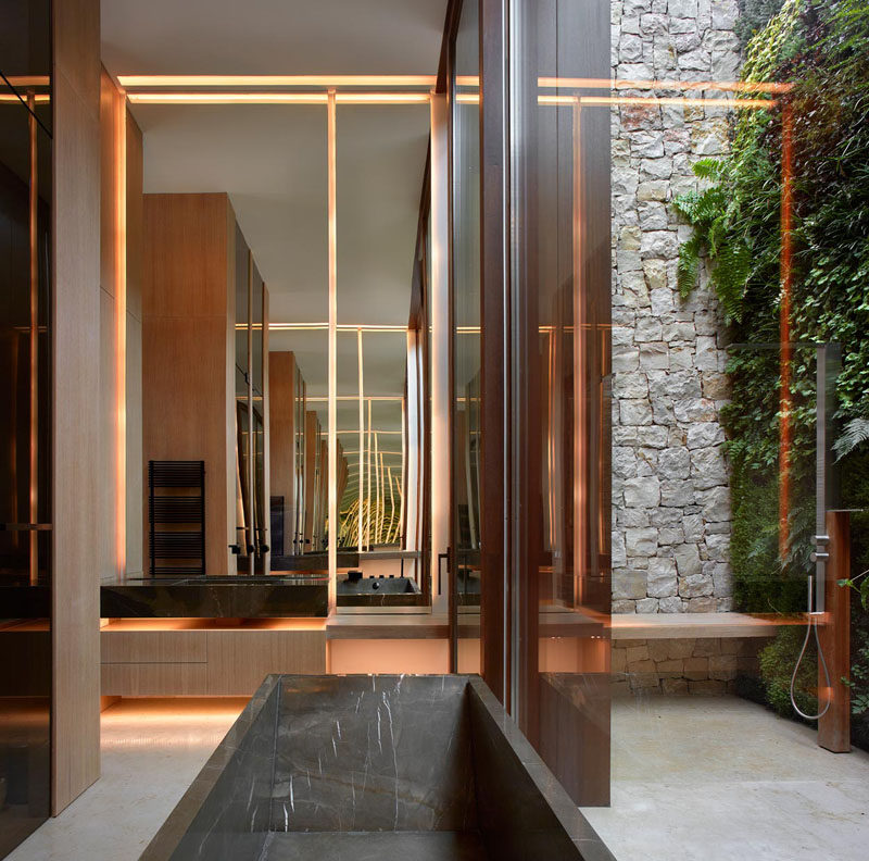 In this modern bathroom, a tall door opens to a private courtyard with a green wall and an outdoor shower. #Bathroom #ModernBathroom #OutdoorShower