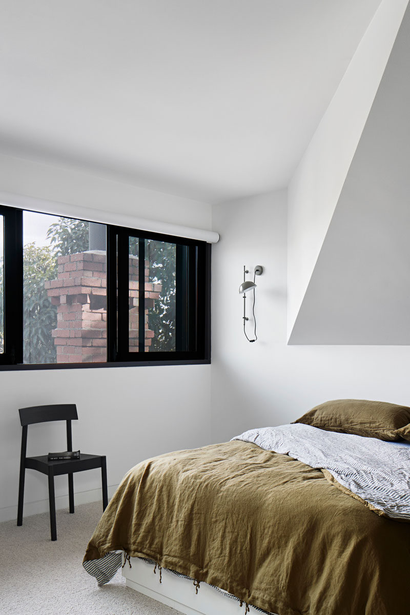 In this modern bedroom, white walls and high ceilings gives the room a lofty feeling, while the windows provide tree views and a glimpse of a brick chimney. #ModernBedroom