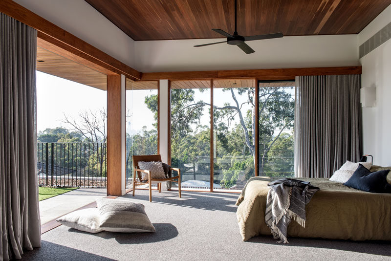 This modern master bedroom has floor-to-ceiling windows, and sliding doors that open up to a green roof overlooking the pool below. #MasterBedroom #Windows #WoodCeiling