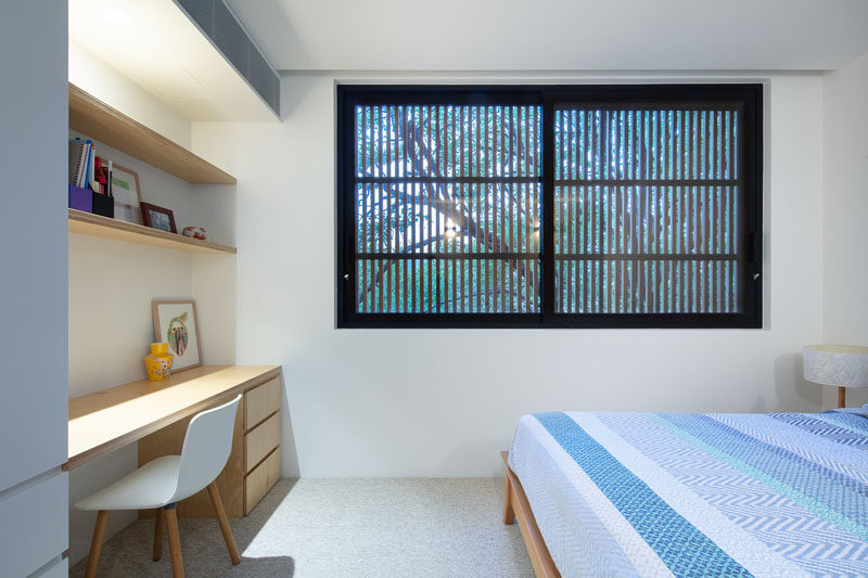 In this modern bedroom, the movable timber batten screens on the exterior of the house provide privacy when closed, while a built-in desk and open shelving have been added between the closet and wall. #Bedroom #Window #Desk