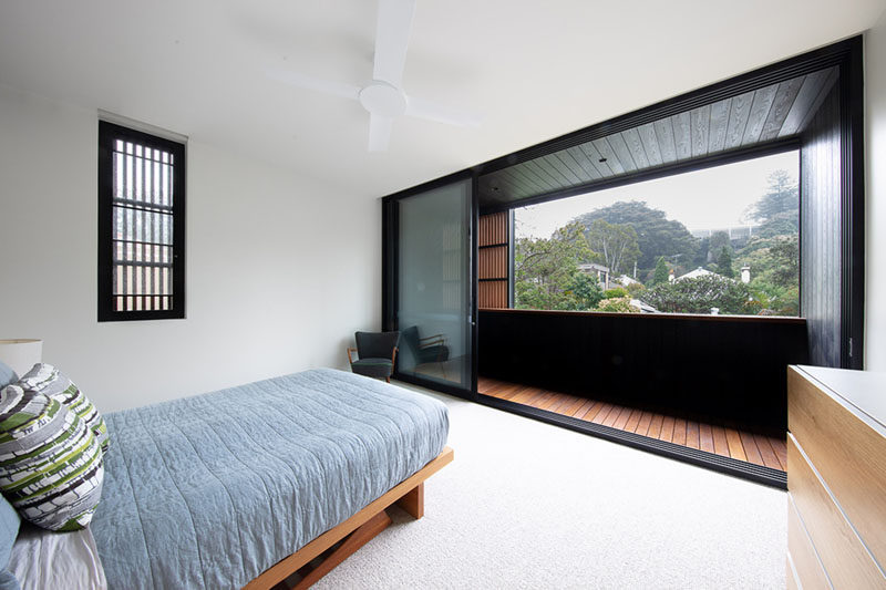This bedroom has minimal furnishings, however it has sliding glass doors that open up to a balcony with treetop views. #ModernBedroom #Balcony