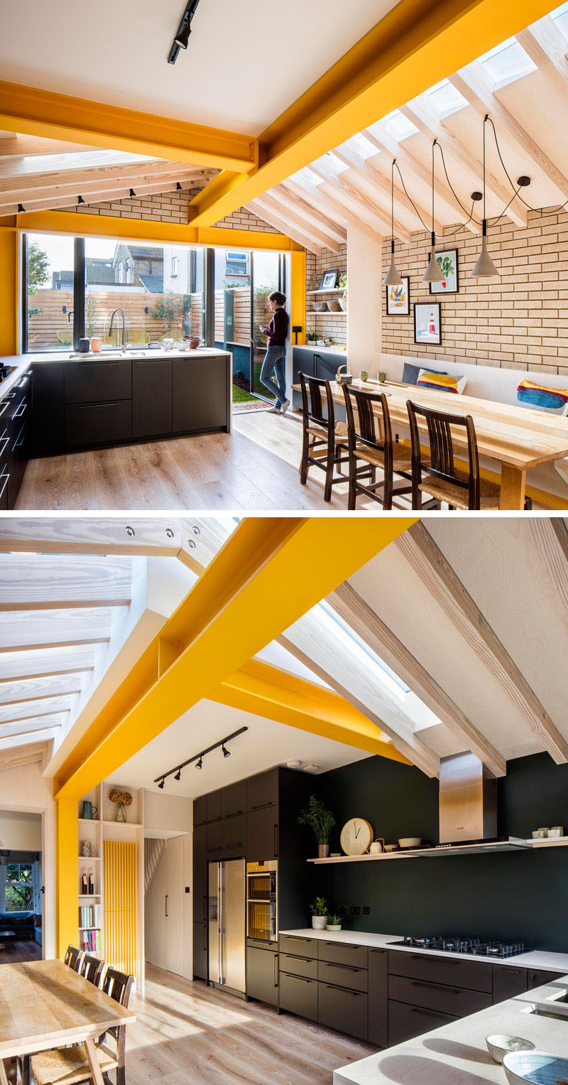 Inside this brick extension by Woodrow Architects, large yellow steel beams provide support, while unconnected rafters sail over with steel plate apex connections allowing the design to do away with any ridge beam.# #YellowBeams #BlackKitchen #BrickExtension Visit Woodrow Architect's website here > https://www.wdrw.co.uk