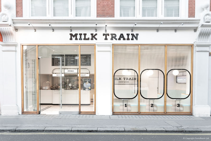 Inspired by trains and train stations, the exterior of the 'Milk Train Cafe' utilizes beaded opaque glass to mimic the steaming of a train window, whilst the black metal detailing lends another subtle nod to the brand's immersive train experience. #CafeDesign #IceCreamStore #RetailDesign