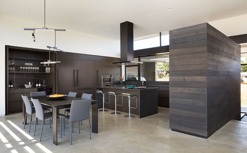 Inside this modern house, dark wood cabinetry has been used in the kitchen, while a minimalist light fixture hangs above the dining table. #DarkWoodKitchen #KitchenDesign #DiningRoom