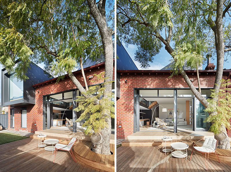 Sliding doors open the interior spaces of this renovated house to the backyard, that features a wood deck with seating that wraps around a large tree. #Backyard #Deck