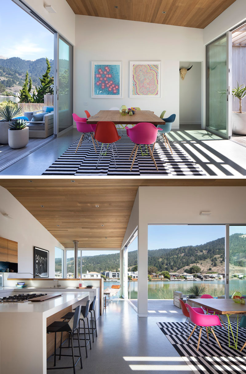 The sliding glass front door of this modern house opens up to the dining room, that has a sloped ceiling, and furnished with a square wood table and colorful chairs.#DiningRoom #Kitchen