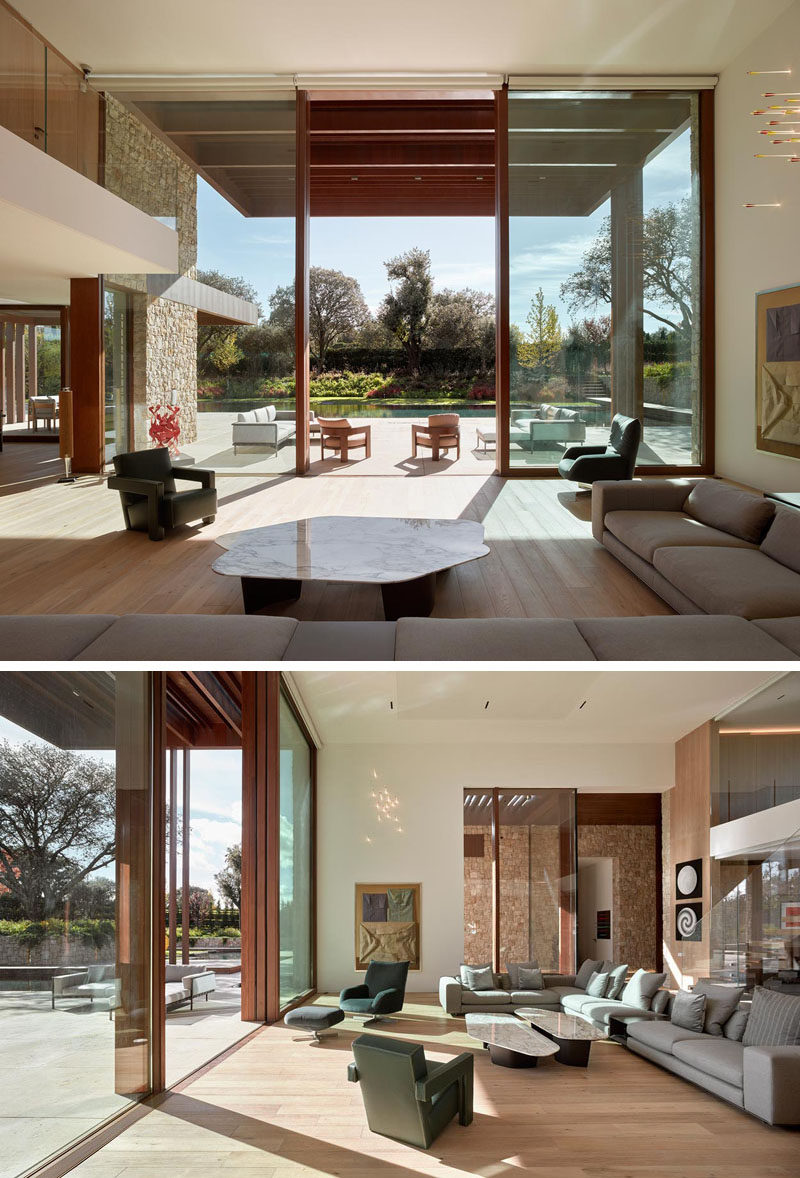 Inside this modern house, double height ceilings in the living room create an open gallery-like atmosphere. #LivingRoom #HighCeilings