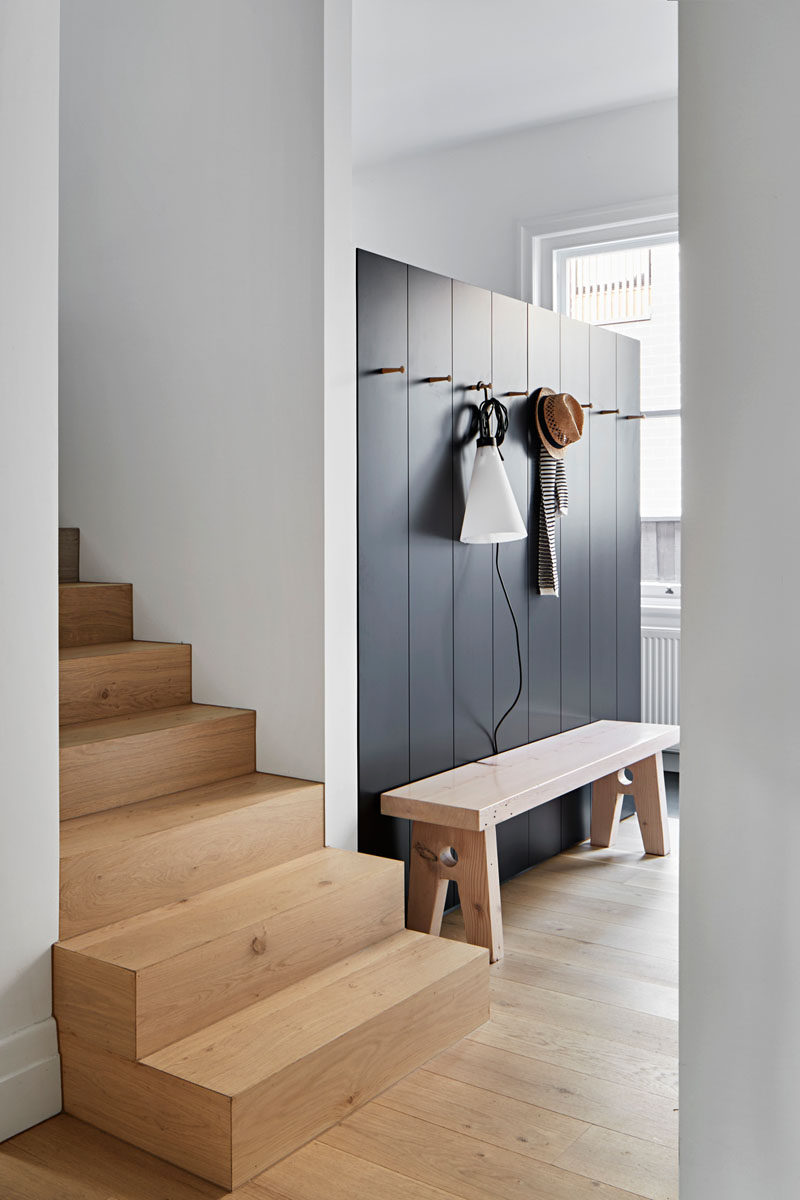 Stepping inside this home, there's a dark accent wall with hooks for hanging up jackets, and a wood bench for taking off shoes. #Entryway #InteriorDesign