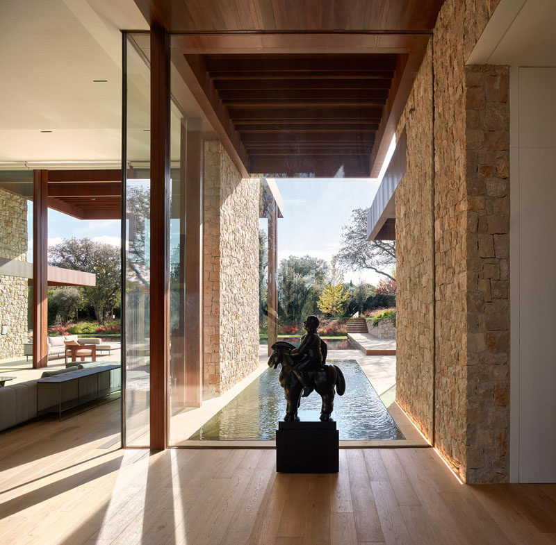 This glass wall provides a backdrop for a statue, and frames the water feature and garden outside. #GlassWall #WaterFeature