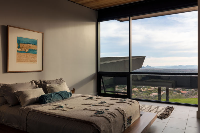 This modern guest bedroom has floor-to-ceiling windows for taking advantage of the view. #GuestBedroom #Windows