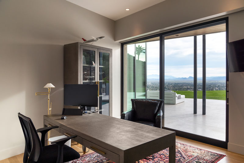 This modern home office has a neutral color palette and sweeping views of the valley. #HomeOffice