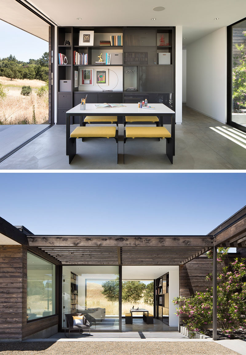 This modern house has a home office with built-in shelving, a communal work table, and a lounge area. Large sliding glass doors open the interiors to the outdoor spaces. #ModernHomeOffice #HomeOffice #ModernHouse