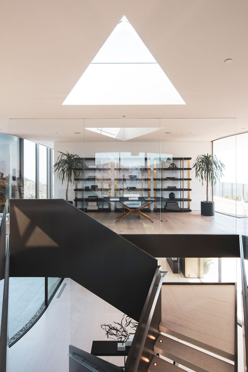 This modern house has a glass enclosed home office that uses shelving as a backdrop for the desk. #HomeOffice #InteriorDesign