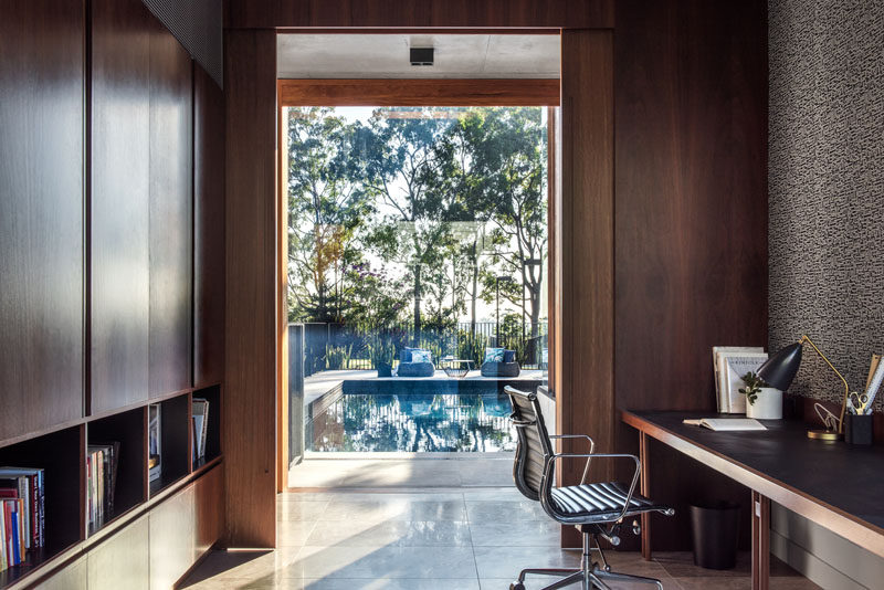 This modern home office features rich wood cabinetry and a view of the pool. #HomeOffice #Cabinets