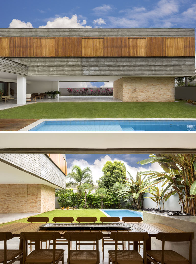 This modern house has a large yard adjacent to the swimming pool, and a covered patio area that's home to an alfresco dining area. #Architecture #SwimmingPool #AlfrescoDining