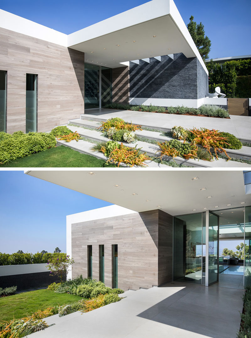 The dark-grey rough stacked-slate exterior of the house is capped with crisply contrasting white stucco, and a pivot-style all-glass front door and surround welcomes guests to this modern house. #Architecture #ModernHouse #GlassFrontDoor