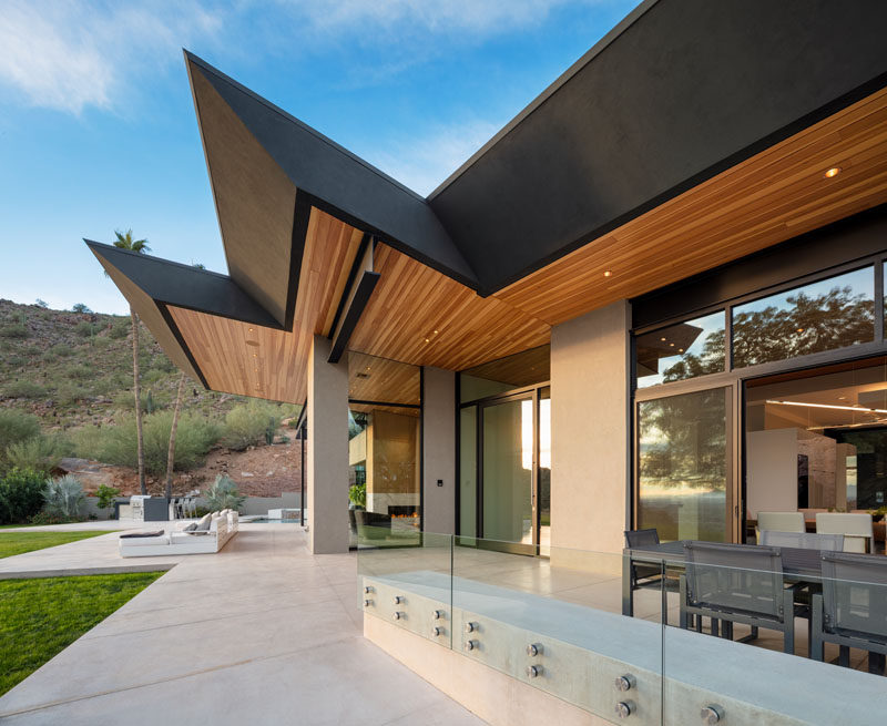 This modern house has a large patio with outdoor dining, a lounge area with a fire pit, and a swimming pool. #Patio #Architecture