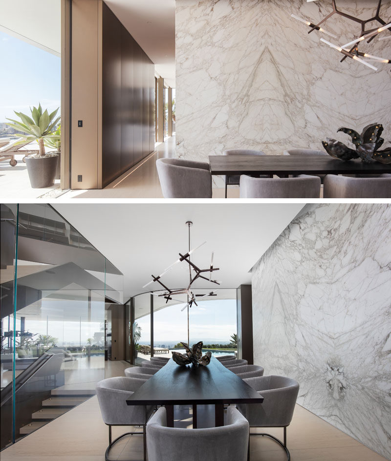 In this contemporary dining room, a stone wall adds a natural touch to the interior, while a minimalist sculptural light hangs above the dining table. #DiningRoom #StoneWall