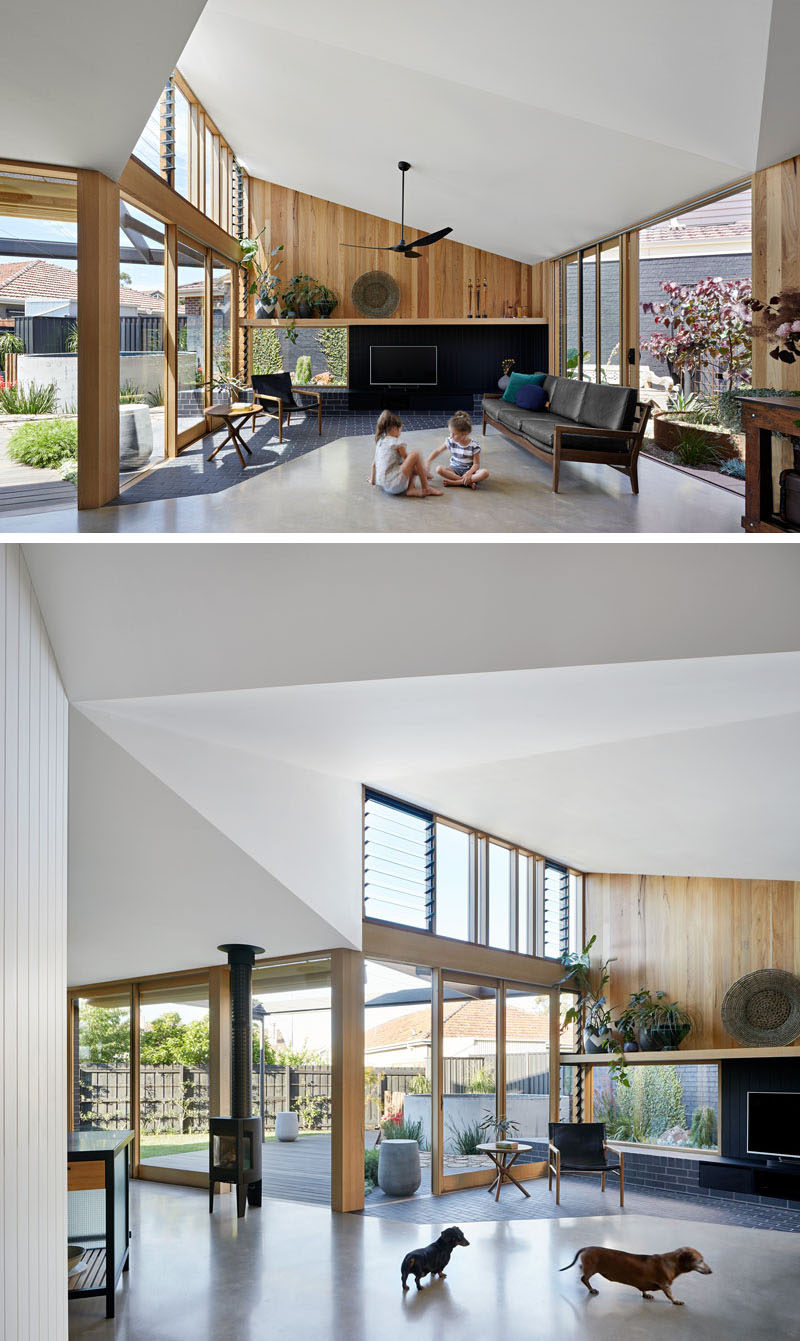 Inside this modern house extension, the high ceilings create a lofty and open feeling for the living room, while the windows flood the space with natural light. The dark brick from the patio outside continues to flow into the living room to meet the concrete floor. #LivingRoom #HouseExtension