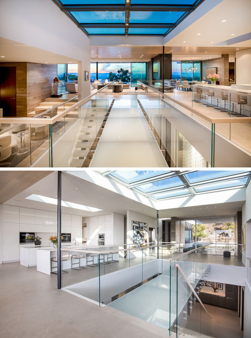 This modern house has a glass bridge that sits below a large skylight, that provides light to the social areas of the house, as well as the lower level. #GlassBridge #Skylight