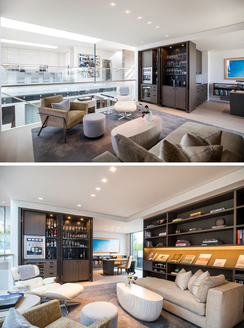 This modern house a library seating area with a built-in bar cabinet, which are open to the central volume and an adjoining home office. #Library #HomeLibrary #Bar #HomeOffice