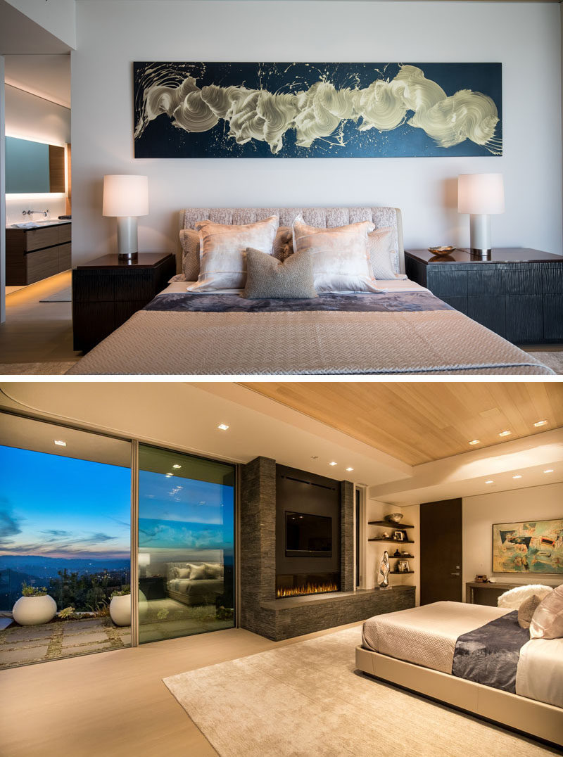 In this modern master suite, there's a painting above the bed by James Nares, and opposite the bed is a fireplace, that sits beside sliding glass doors that open to the back patio. #MasterBedroom #Fireplace #BedroomDesign