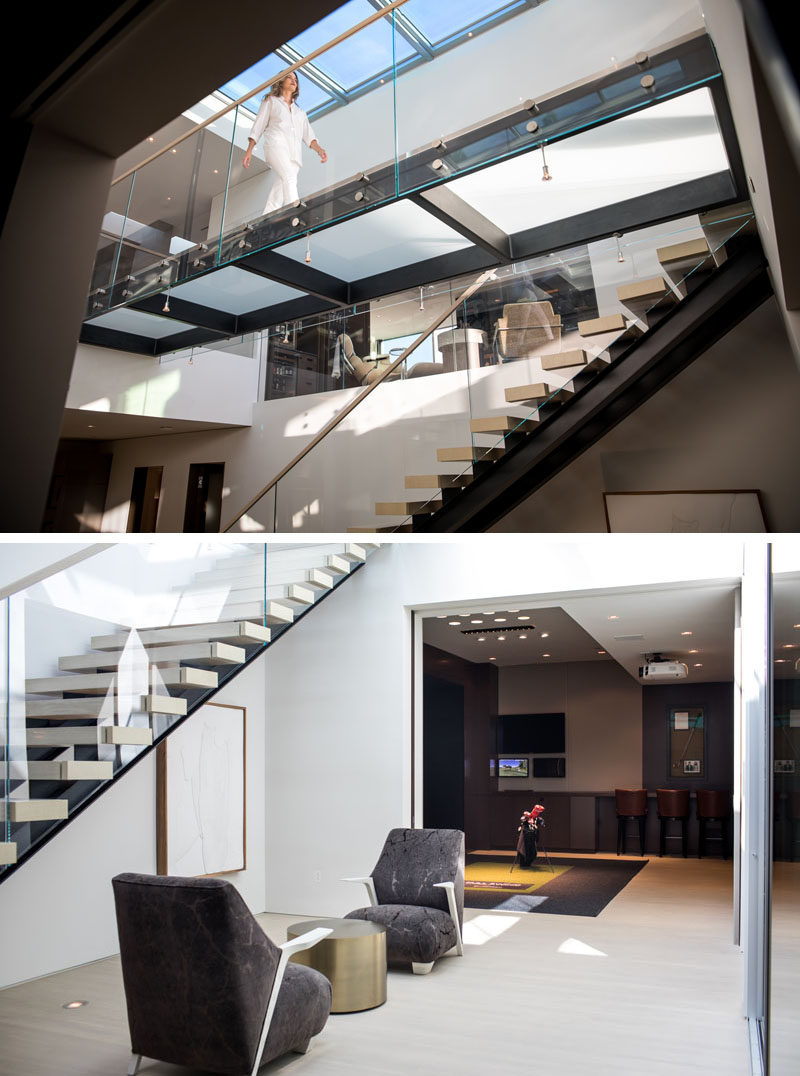 This modern house has floating stairs that lead down to the bottom level of the home. The downstairs courtyard area, lit by the skylight, includes a small seating area and wine storage. #Stairs #ModernStairs #Skylight