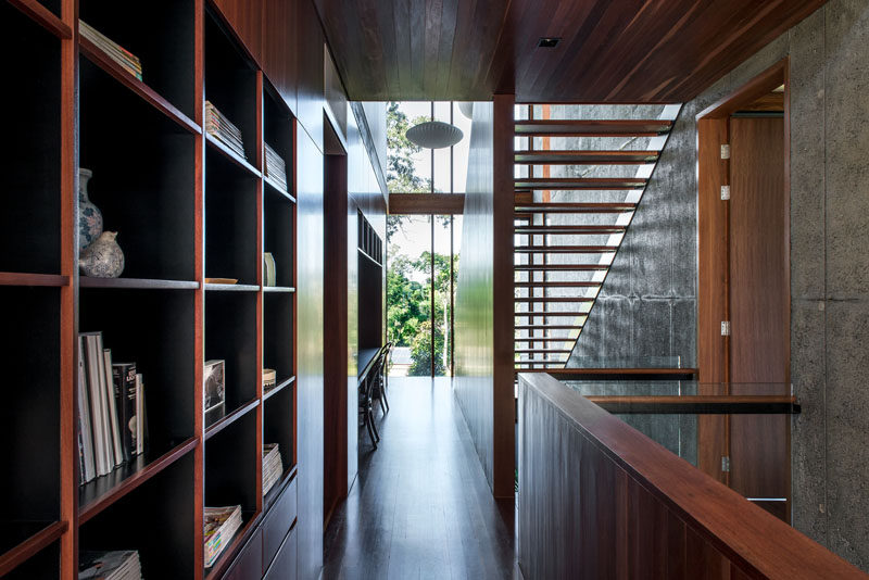Rich wood cabinetry, open shelving, and a built-in desk, feature the hallway of this modern house. #Shelving #Cabinetry