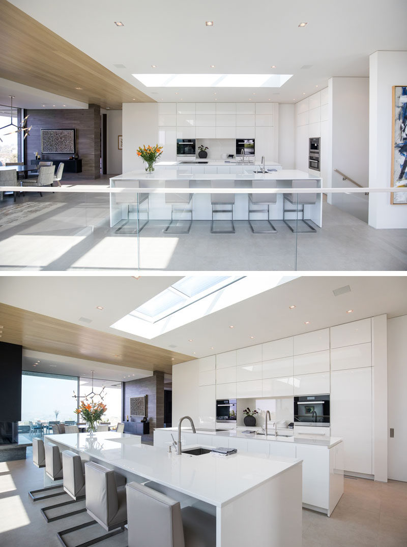 This modern house has sleek all-white kitchen islands and floor-to-ceiling cabinets that are minimalist in their design, with a skylight adding even more light to the bright space. #WhiteKitchen #ModernKitchen #KitchenDesign
