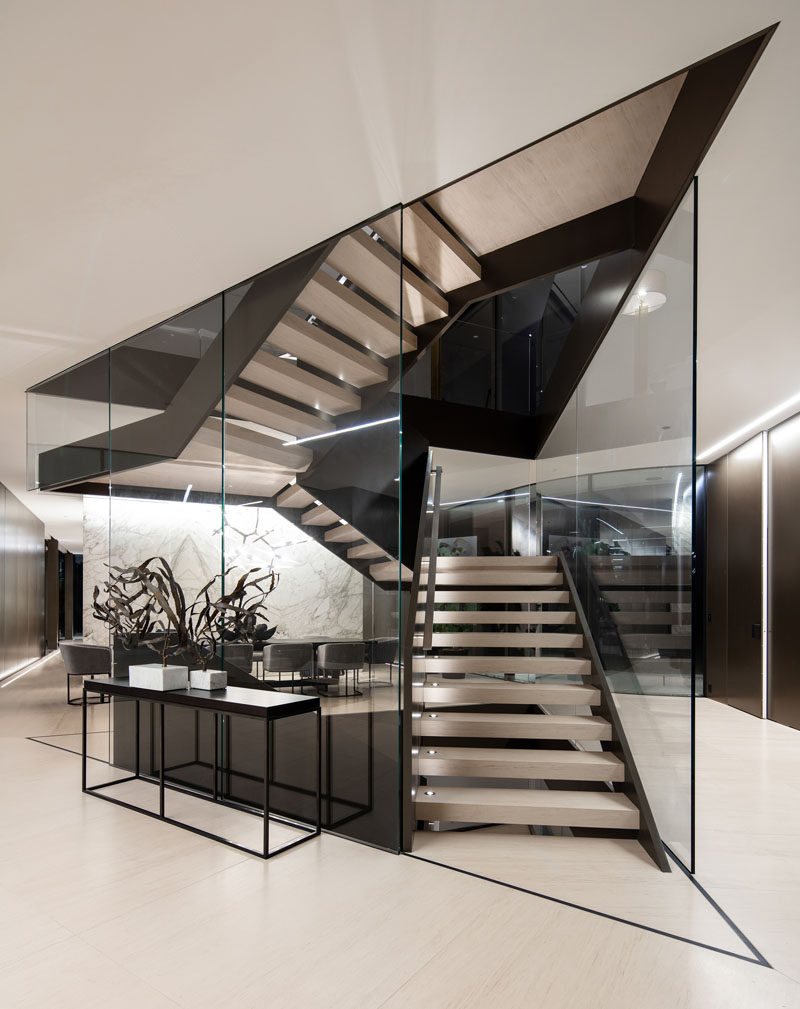 A large and sculpture staircase made of metal and glass is central to this modern house. #Staircase #ModernStairs
