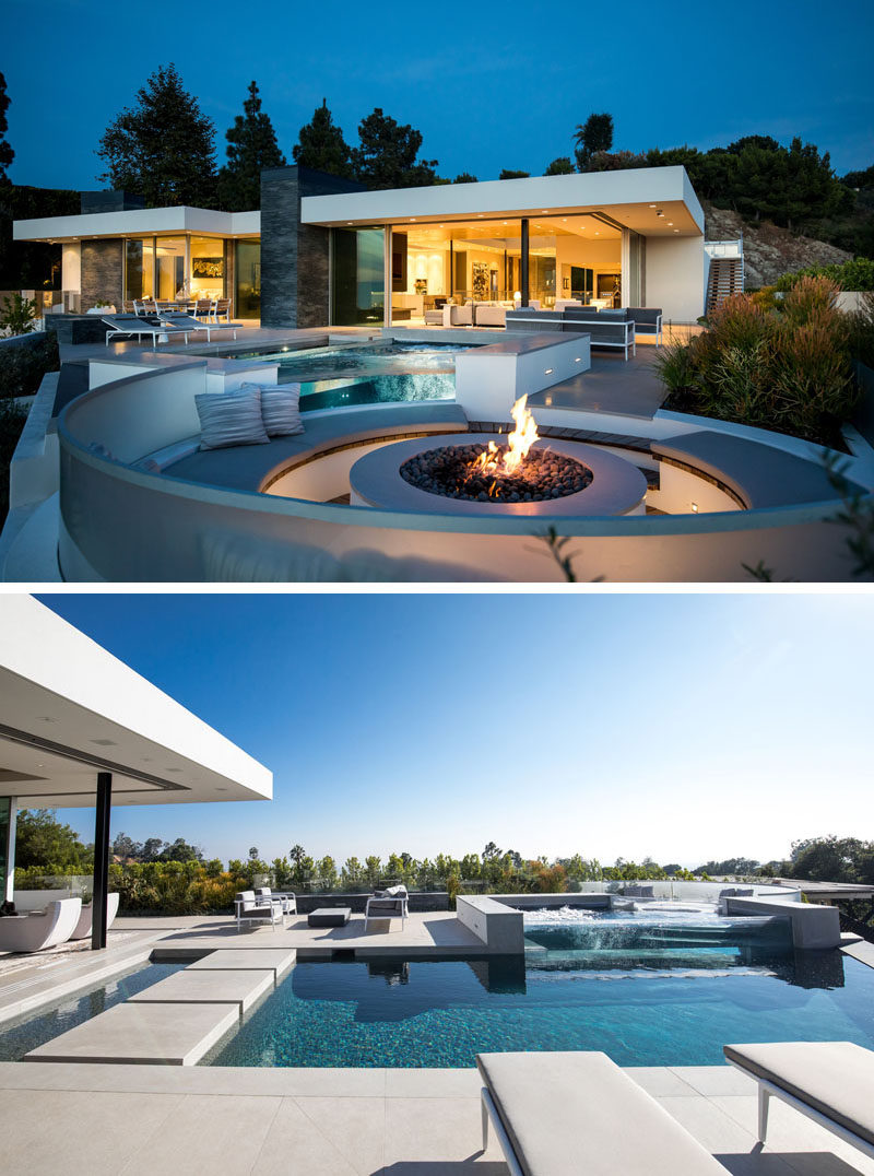 At the back of this modern house, two walls of glass glide open to provide easy access to the pool and patio entertaining spaces, including a circular fire pit with seating. #Patio #SwimmingPool #FirePit
