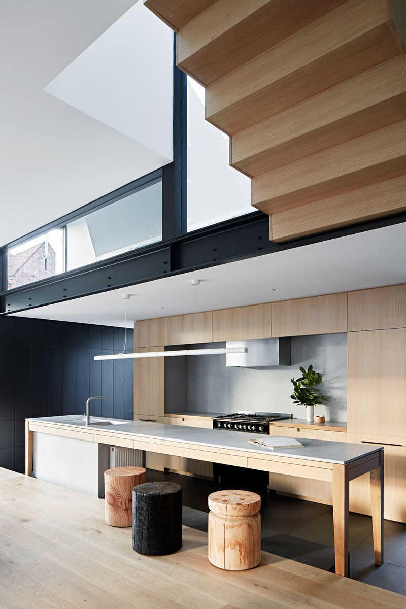 In this modern kitchen, a long island provides ample food prep area, while minimalist wood cabinetry lines the wall. #KitchenDesign #ModernKitchen