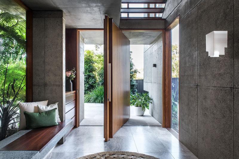 A large pivoting wood front door welcomes visitors to this modern house. #FrontDoor #PivotingDoor #WoodDoor