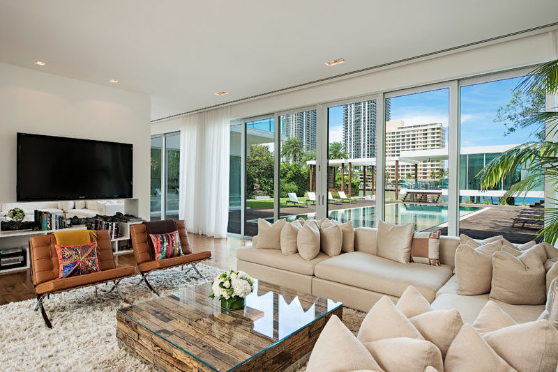 Sliding glass doors open this living room to the wood deck that surrounds the swimming pool. #LivingRoom