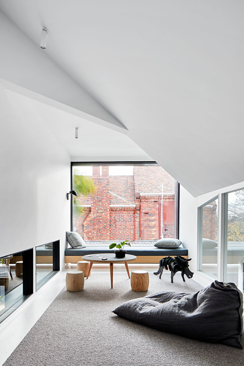 This modern house has a playroom with a built-in window seat that takes advantage of the large picture window. #Playroom #WindowSeat
