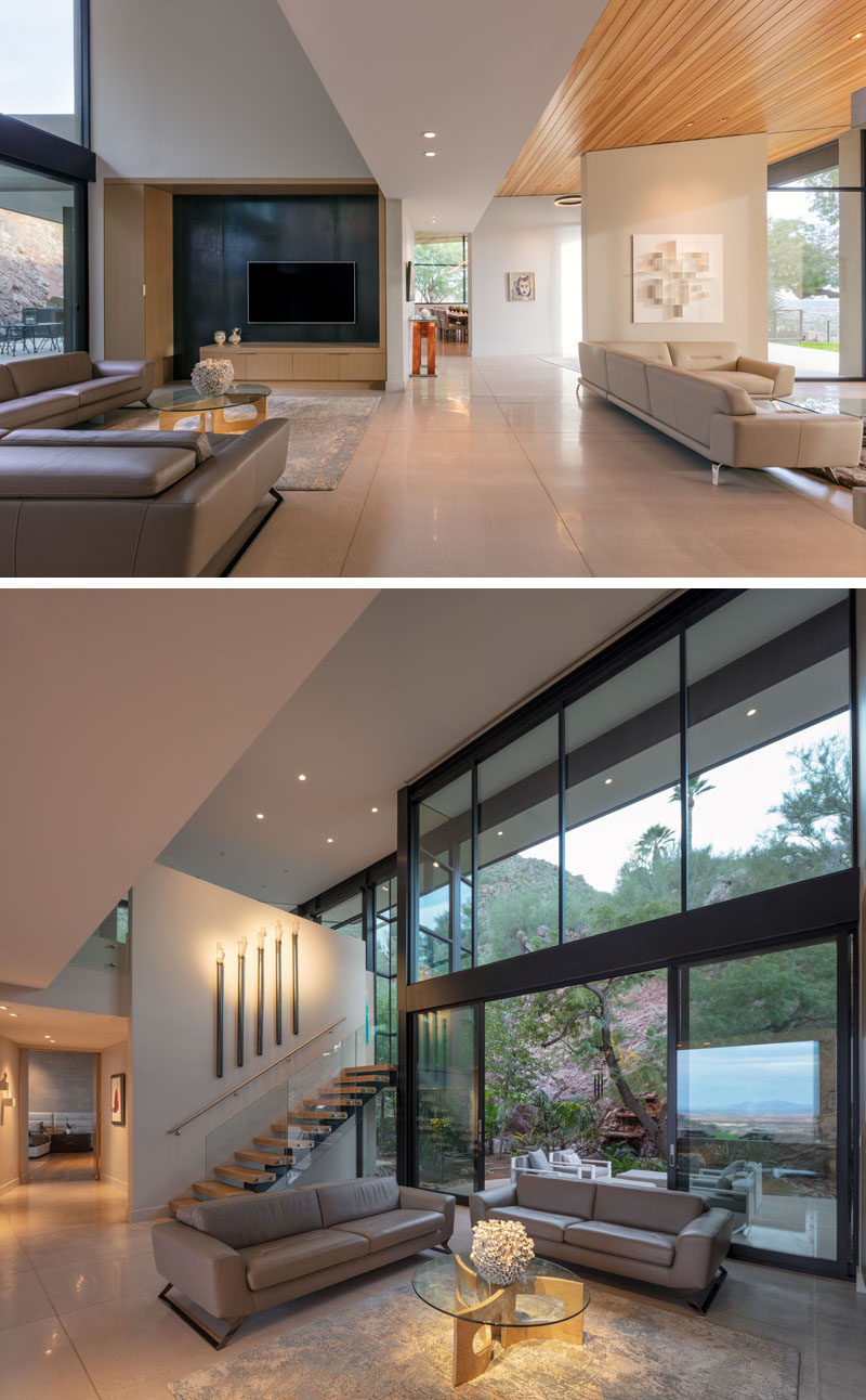 This modern house has a casual living room with a high ceiling and access to a small patio outside. #LivingRoom #Windows