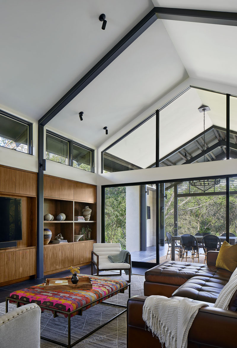 A light-filled living room with high ceilings and built-in cabinetry was added to the back of this modern house. #ModernLivingRoom #LivingRoom #HighCeiling