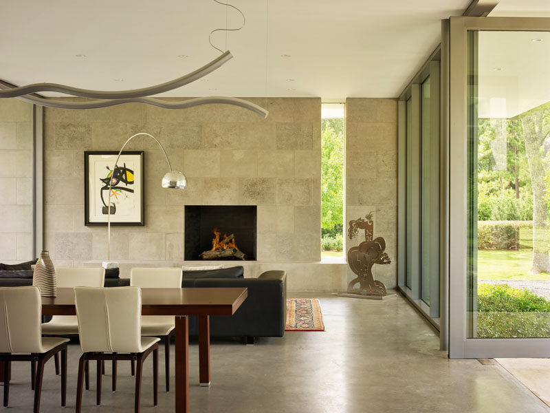Inside this modern house, a limestone wall surrounds a fireplace, while the floor-to-ceiling windows provide views of garden. #LimestoneWall #InteriorDeisgn