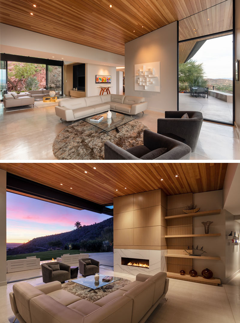 This modern living room has a fireplace and open shelving, while large sliding glass doors open the room to the outdoors. #LivingRoom #Fireplace #Shelving