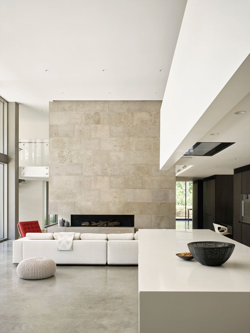 This modern house features high ceilings, and a large limestone wall that surrounds a fireplace in the living room. #HighCeilings #LivingRoom #LimestoneWall