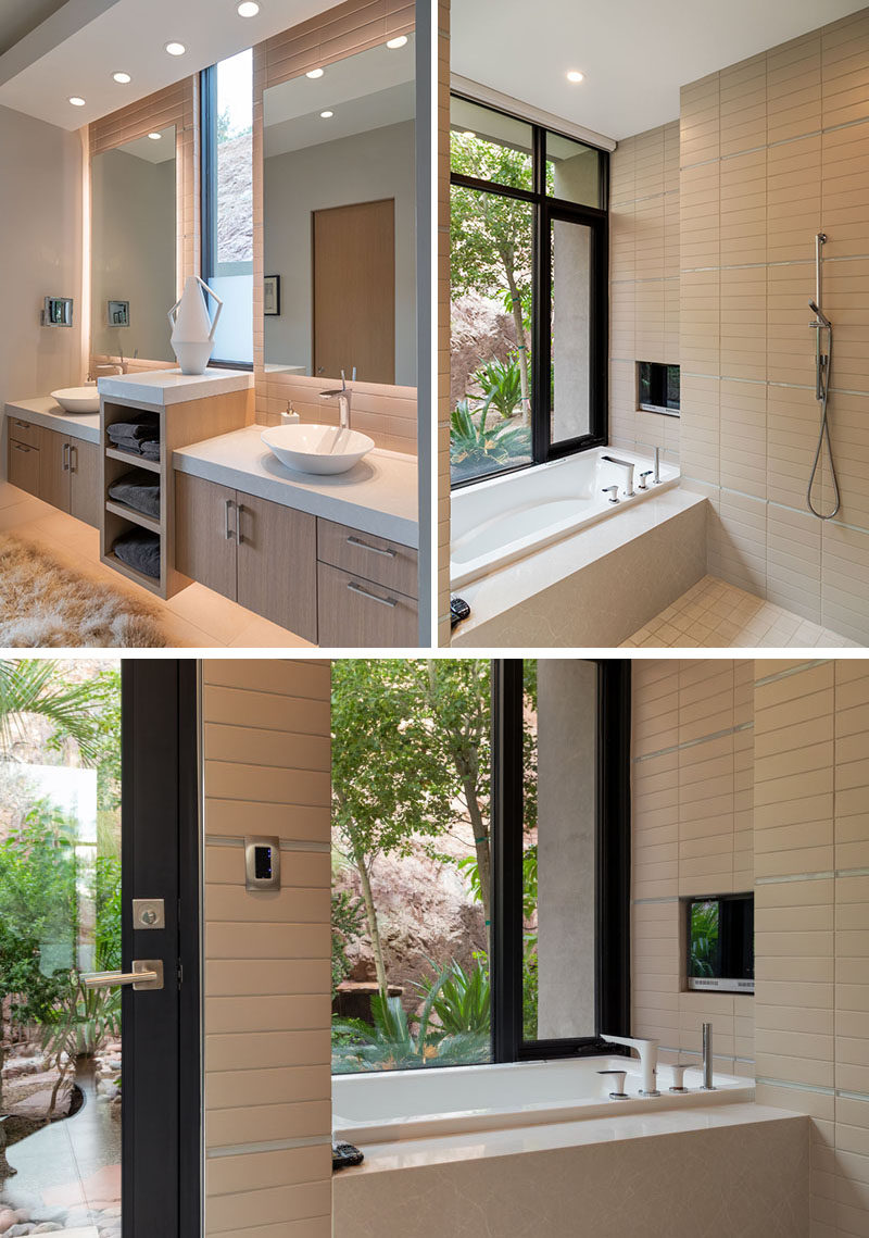 In this master bathroom, floor-to-ceiling tiles cover the walls and dual vanities makes sure there's plenty of counter space and storage. The bathroom also opens to a small private patio surrounded by plants. #ModernBathroom #MasterBathroom #BathroomDesign