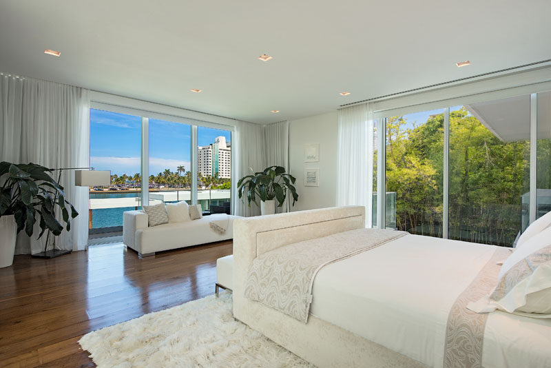 Floor-to-ceiling windows provide water and palm tree views for this modern master bedroom. #MasterBedroom #BedroomDesign #Windows