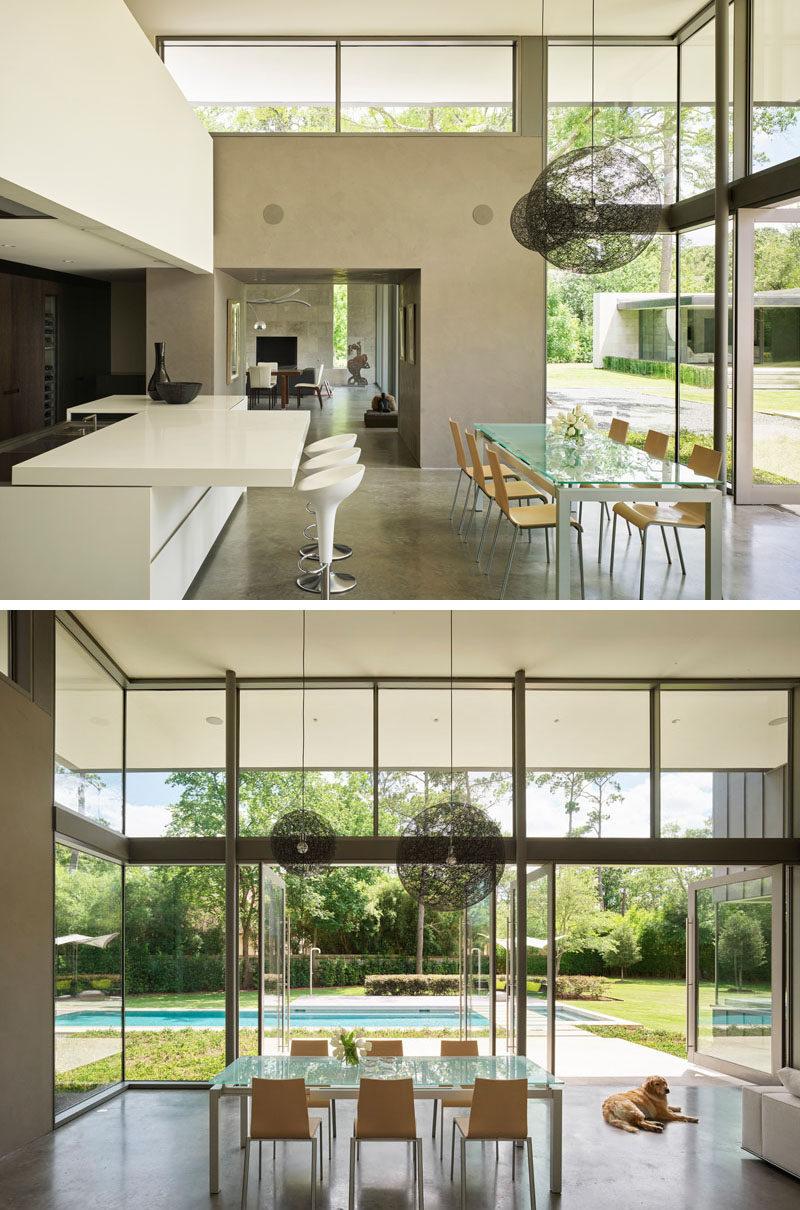 At the heart of this modern house is a double-height great room encompassing family living, a dining area and kitchen. #ModernInterior #HighCeilings #PivotDoors