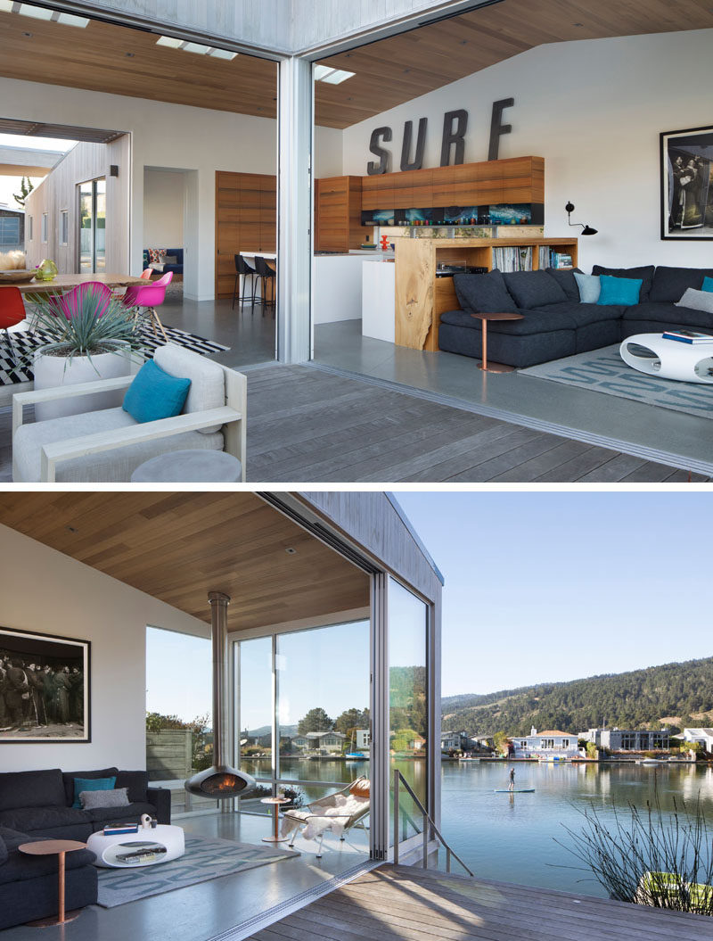 The main social areas of this modern house are all open plan, with a wood shelving unit separating the living room from the dining room. Large sliding glass doors open to create an indoor/outdoor living environment. #InteriorDesign #ModernHouse