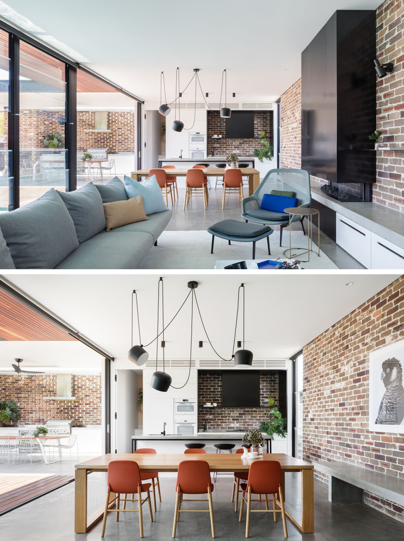In this open plan living room, dining room, and kitchen, there's a recycled brick wall that wraps around the room, and provides a backdrop for the black fireplace and concrete bench. #InteriorDesign #Brick #OpenPlanInterior