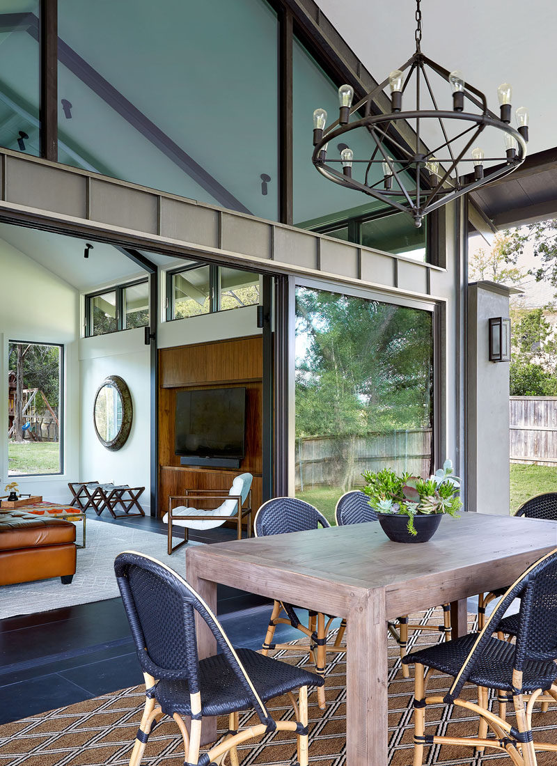 The living room of this modern house opens to a new covered outdoor living space, that's been furnished with an alfresco dining area. #OutdoorDining #ModernHouse