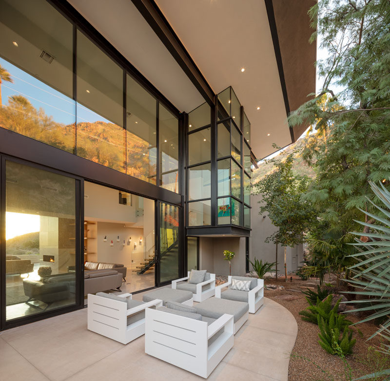 This modern house has a small patio that's located against the hillside, and is furnished with outdoor armchairs. #Patio #Landscaping #ModernHouse