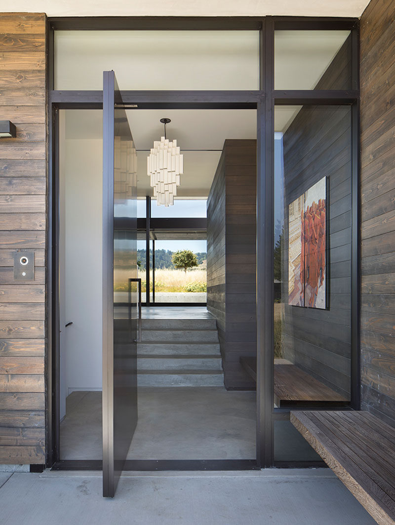 Welcoming visitors to this modern house is a large pivoting front door that opens up to the social areas of the home. #PivotingFrontDoor #FrontDoor