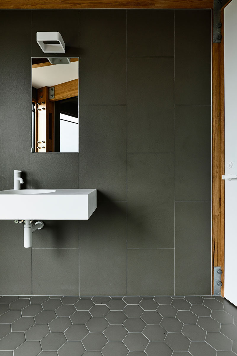 In the bathroom, large format tiles cover the walls, while smaller hexagonal tiles cover the floor. #Tiles #GreyTiles #Bathroom